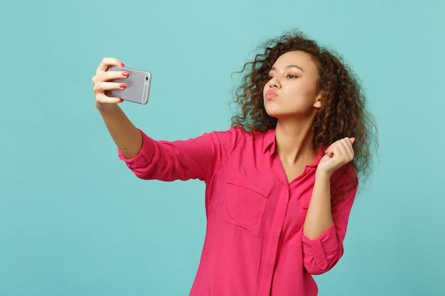 Carina ragazza africana in abiti casual che soffia invio bacio d'aria, facendo selfie girato sul telefono cellulare isolato su sfondo blu turchese. persone sincere emozioni, concetto di stile di vita. mock up copia spazio.