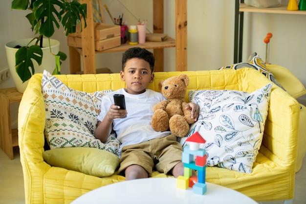 Simpatico bambino in età prescolare africano con telecomando e orsacchiotto marrone che ti indica mentre giaceva sul pavimento del soggiorno