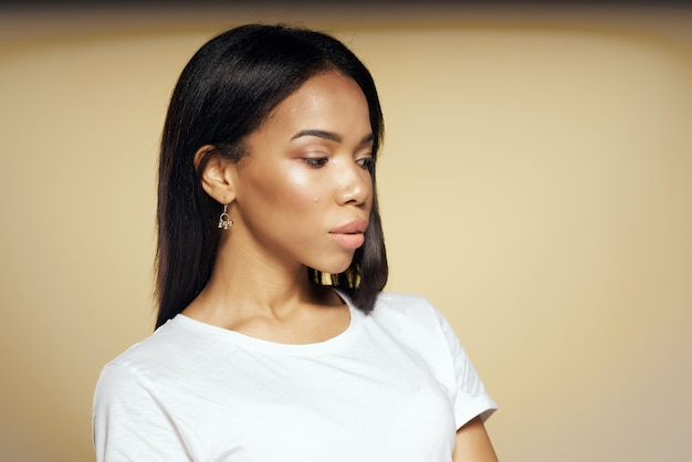 Donna africana carina in maglietta bianca con i capelli lunghi in posa da vicino