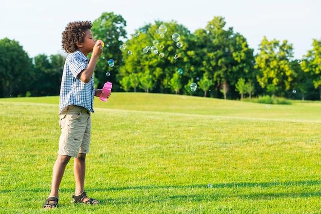 Il simpatico ragazzo afro sta facendo le bolle sulla radura soleggiata