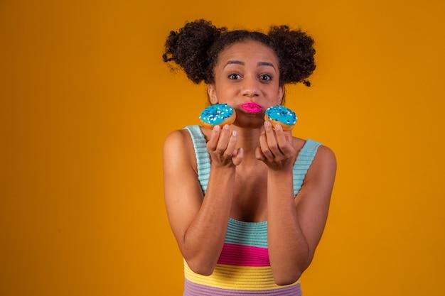 Carina ragazza afro che tiene due ciambelle colorate. donna afro con ciambelle
