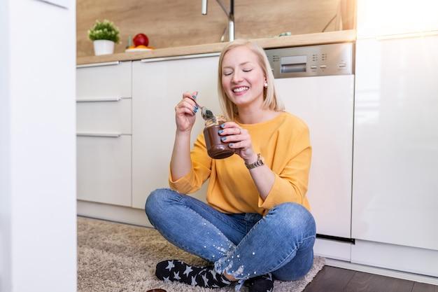 Giovane donna sveglia dell'albino in vestiti alla moda moderni che gode della diffusione saporita del cioccolato con il sorriso sveglio all'interno della cucina.