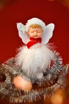 Decorazione di natale angelo carino su sfondo rosso. copia spazio. biglietto d'auguri. anno nuovo e buon natale