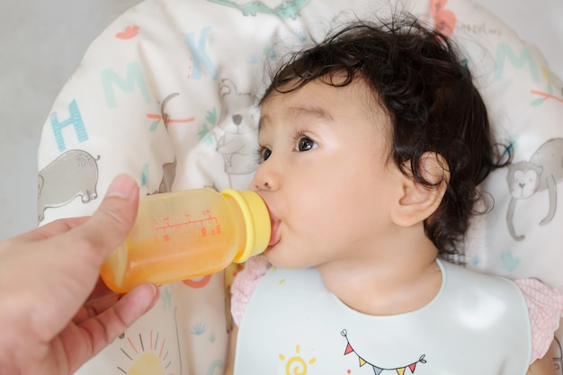 Un simpatico bambino asiatico che beve succo d'arancia dalla mano della madre che tiene la bottiglia