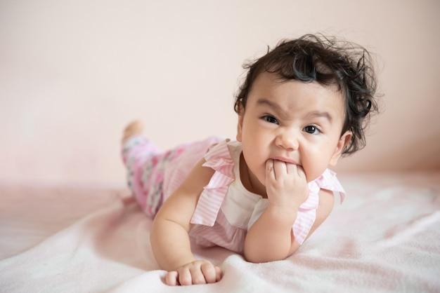 Carina bambina asiatica sdraiata sul letto e mordendosi la mano guarda la telecamera