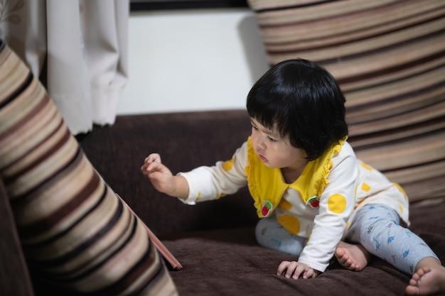 Bambino asiatico sveglio guardando il telefono cellulare e seduto sul divano