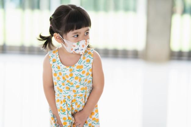 Simpatico bambino asiatico che indossa una maschera per proteggere il coronavirus.