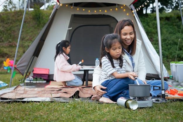 Ragazza asiatica sveglia del bambino divertendosi per aiutare sua madre che cucina fuori dalla tenda mentre si accampa con la famiglia.