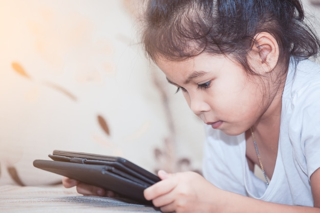 Ragazza asiatica sveglia del bambino che si riposa e che utilizza smart phone, compressa nella stanza