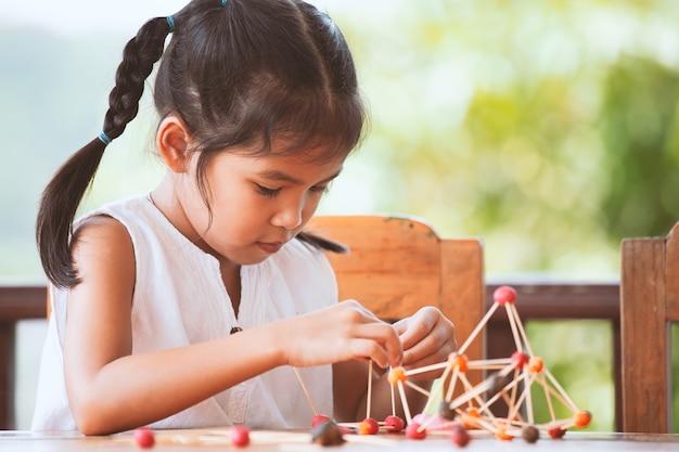 Ragazza carina asiatica bambino giocando e creando con pasta e stuzzicadenti. Foto Premium