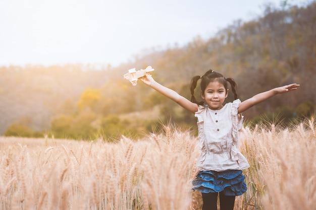 Ragazza asiatica sveglia del bambino che corre e che gioca con l'aeroplano di legno del giocattolo nel campo dell'orzo