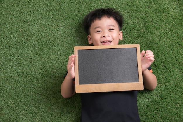 Bambino asiatico sveglio che si trova e che tiene lavagna su erba verde green