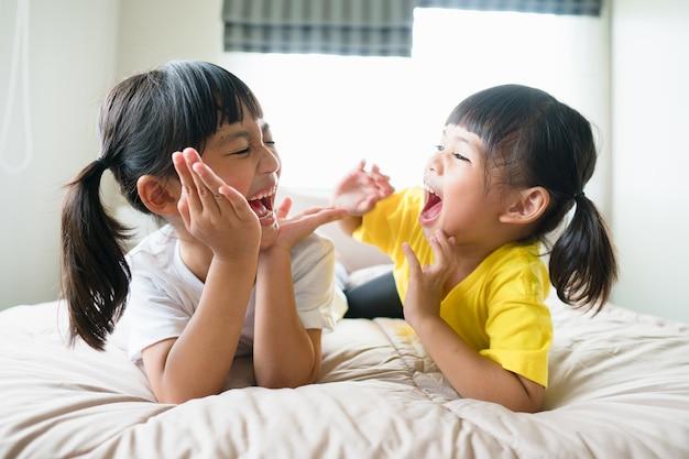 Simpatici bambini asiatici sdraiati sul letto