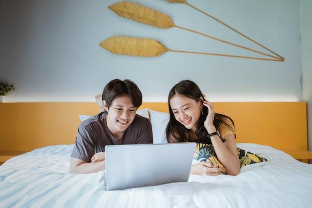 Coppie asiatiche sveglie che si rilassano insieme sul letto facendo uso del computer portatile a casa nella camera da letto
