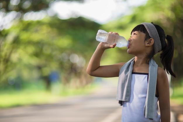 Carina ragazza asiatica beve acqua da una bottiglia all'aperto con la luce del sole