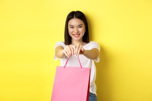 Carina ragazza asiatica che ti fa un regalo, allunga la mano con la borsa della spesa rosa e sorride, congratulandosi con le vacanze, in piedi su sfondo giallo.