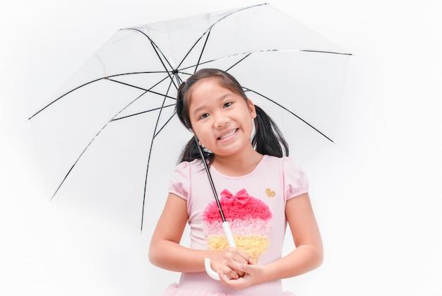 La ragazza asiatica sveglia che sorride e tiene l'ombrello