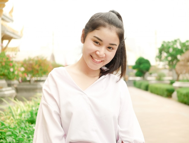 Una ragazza asiatica carina, in un momento di viaggio, lei in posa e sorride per fare una foto all'aperto.