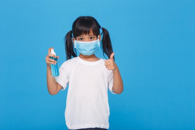 Ragazza asiatica sveglia che indossa una maschera e che tiene il gel dell'alcool
