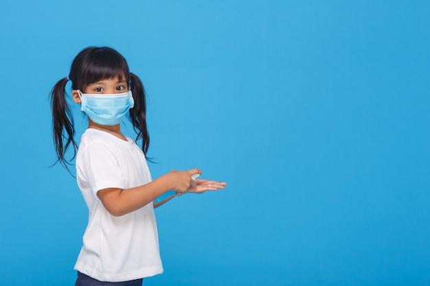 Ragazza asiatica sveglia che indossa una maschera e che lava le sue mani con alcool