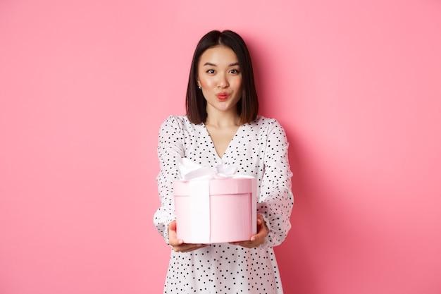 Carina ragazza asiatica si congratula con il giorno di san valentino dando un regalo romantico carino nella scatola labbra increspate ...