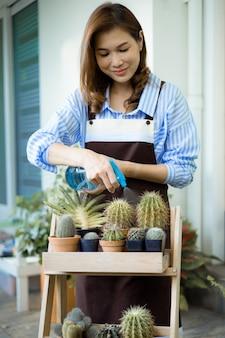 Carina casalinga asiatica che indossa un grembiule con in mano uno spruzzatore d'acqua e innaffia il vaso di piccole piante e cactus con la faccia sorridente e felice con l'hobby a casa nel tempo libero.