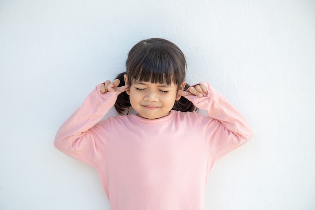 Una ragazza asiatica carina ha coperto le orecchie con le dita e gesticolando che non vuole ascoltare su sfondo bianco con spazio di copia vuoto
