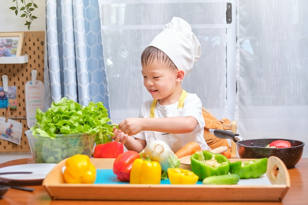 Cappello e grembiule d'uso del cuoco unico del bambino asiatico sveglio del ragazzino divertendosi preparando, cucinando alimento sano in cucina