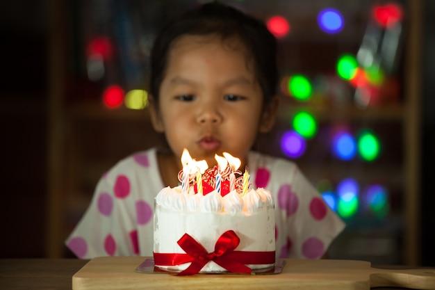 Bambina asiatica sveglia che celebra compleanno e soffiando le candeline sulla torta di compleanno