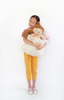 Bambina asiatica carina che abbraccia la borsa dei giocattoli per la donazione. borsa per le coccole delle bambole su bianco