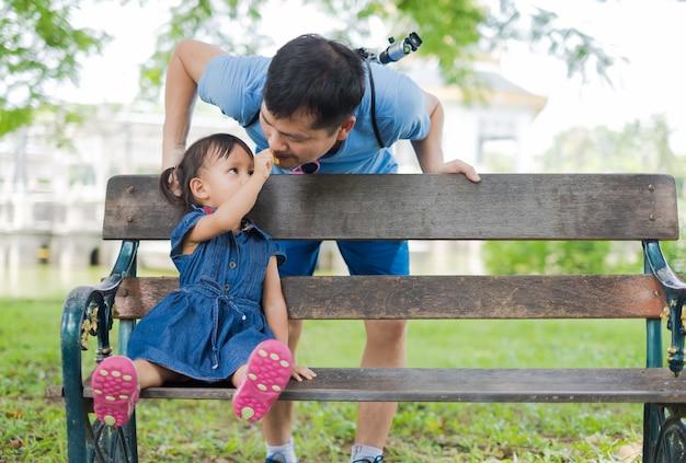 La bambina asiatica sveglia dà i biscotti a suo padre nel parco pubblico verde