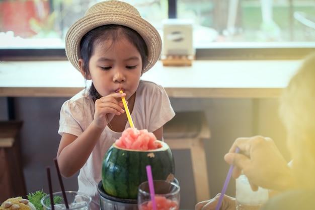 La bambina asiatica sveglia sta bevendo il succo mescolato anguria nel ristorante
