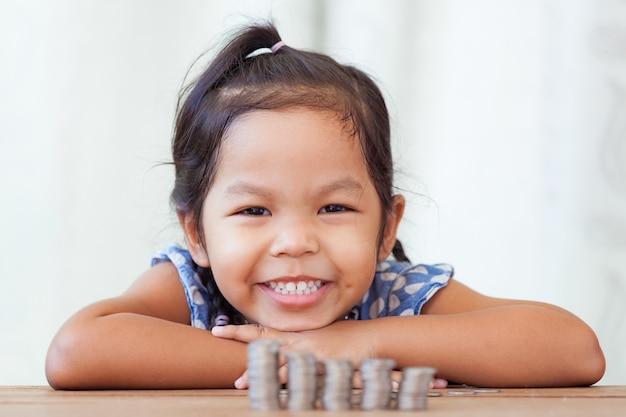 Bambina asiatica carina facendo pile di monete.