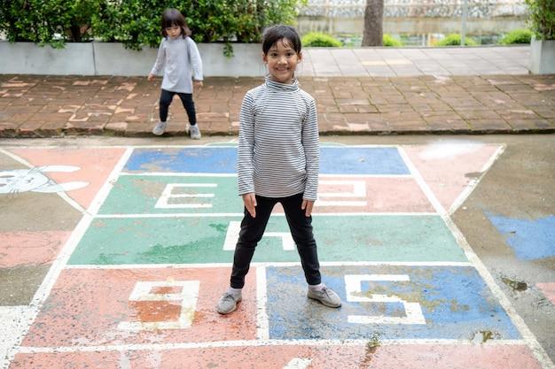 Bambina asiatica sveglia che gioca a campana all'aperto. divertente gioco di attività per bambini nel parco giochi esterno. sport di strada estivo nel cortile per bambini. stile di vita felice dell'infanzia.
