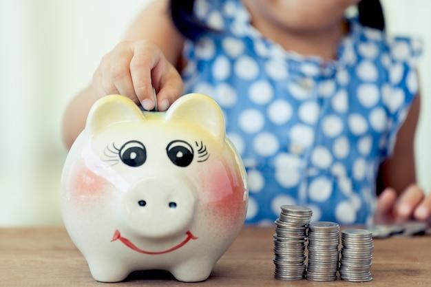 Bambina asiatica sveglia che risparmia soldi nel suo porcellino salvadanaio