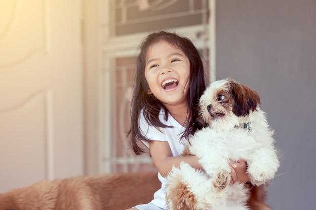 Bambina asiatica sveglia con il suo cane di shih tzu nel tono d'annata di colore