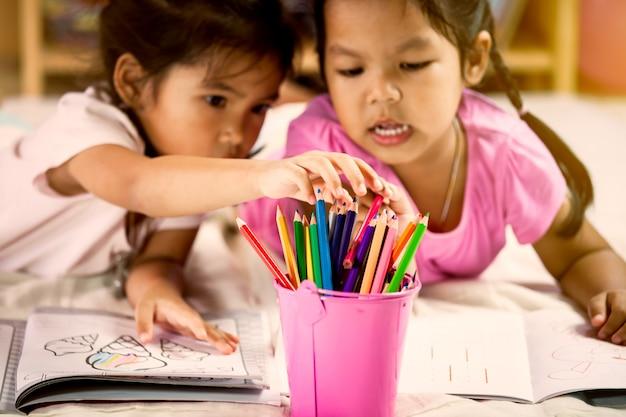 Le bambine asiatiche sveglie disegnano con i loro pastelli. tonalità di colore vintage
