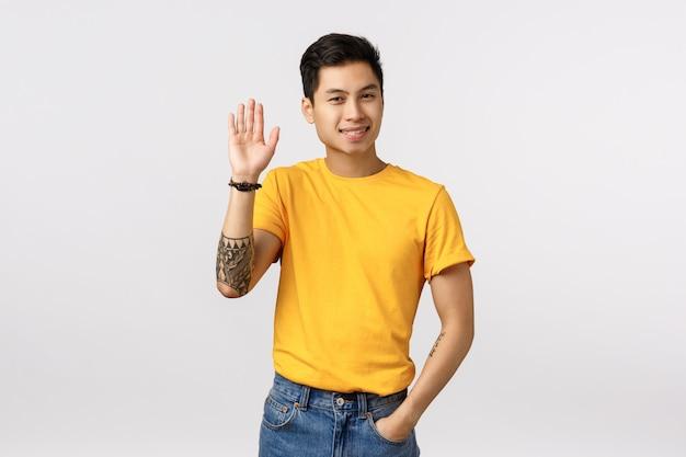 Uomo asiatico sveglio in maglietta gialla che dice ciao