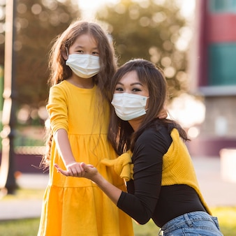 Madre asiatica sveglia e figlia che indossano maschere mediche