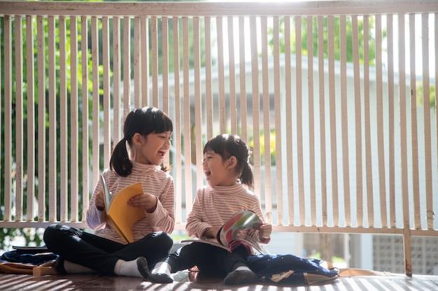 Ragazza asiatica sveglia dei fratelli germani che legge un libro a casa.