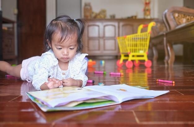 Bambino asiatico sveglio della neonata del bambino che si trova mentre gioca con il libro degli adesivi a casa