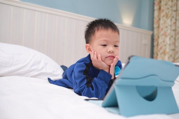 Bambino asiatico sveglio del ragazzo del bambino sdraiato sulla pancia mentre gioca, guardando i cartoni animati, utilizzando il computer tablet pc, bambini dipendenti da gadget, tablet di apprendimento per bambini, concetto di giocattolo educativo del bambino