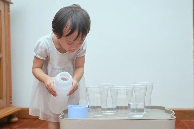 Ragazza carina asiatica del bambino che si diverte a giocare con la falda acquifera a casa, bagnato versando attività di vita pratica prescolare montessori, sviluppo di abilità motorie fini