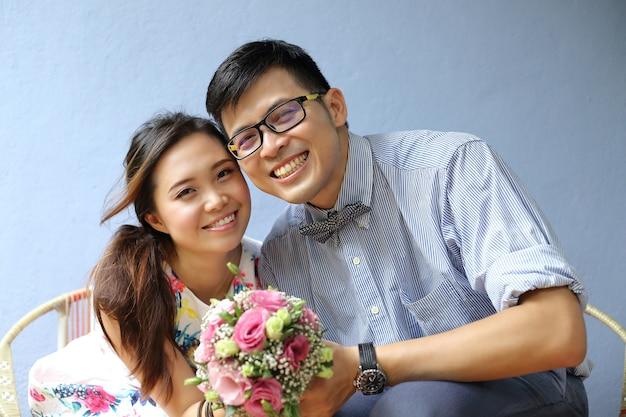 Simpatico servizio fotografico di matrimonio asiatico con sfondo di parete di colore blu antico