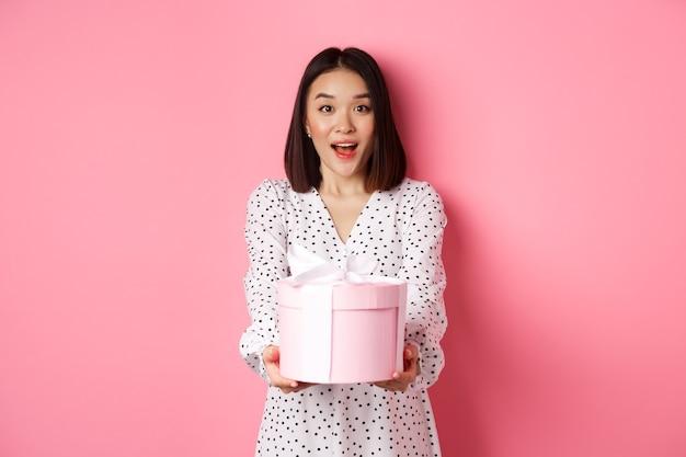 La donna asiatica sveglia si congratula con la festa o il compleanno, dando il regalo nella scatola carina, in piedi sopra il rosa