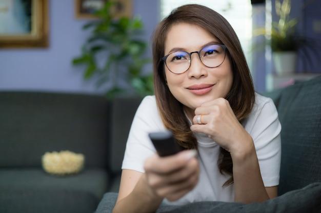 Carina donna asiatica sdraiata sul divano con un gesto rilassante e accogliente che tiene il telecomando che punta alla tv, guarda la televisione e sorride divertito e felice con la sfocatura dei popcorn sullo sfondo. idea hobby e relax.