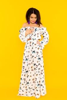 Carina donna asiatica in abito di seta con farfalle in posa sullo spazio giallo