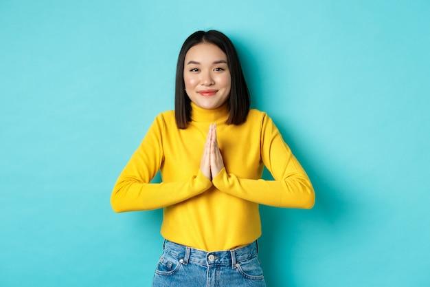 Carina donna asiatica in abito alla moda che dice grazie, tenendosi per mano in namaste, implorando gesto, sorridendo grato alla telecamera, in piedi su sfondo blu