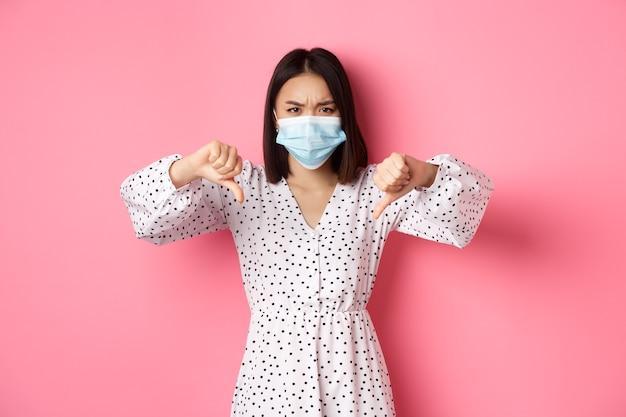 Donna asiatica sveglia che indossa vestito e maschera medica