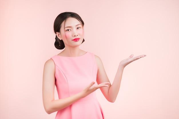 Carina giovane donna asiatica con la mano di gesto di trucco di moda che mostra qualcosa di isolato sul rosa.